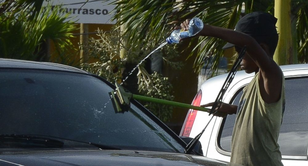 Nos estacionamentos à beira-mar, crianças trabalham lavando o vidro dos carros em Natal.