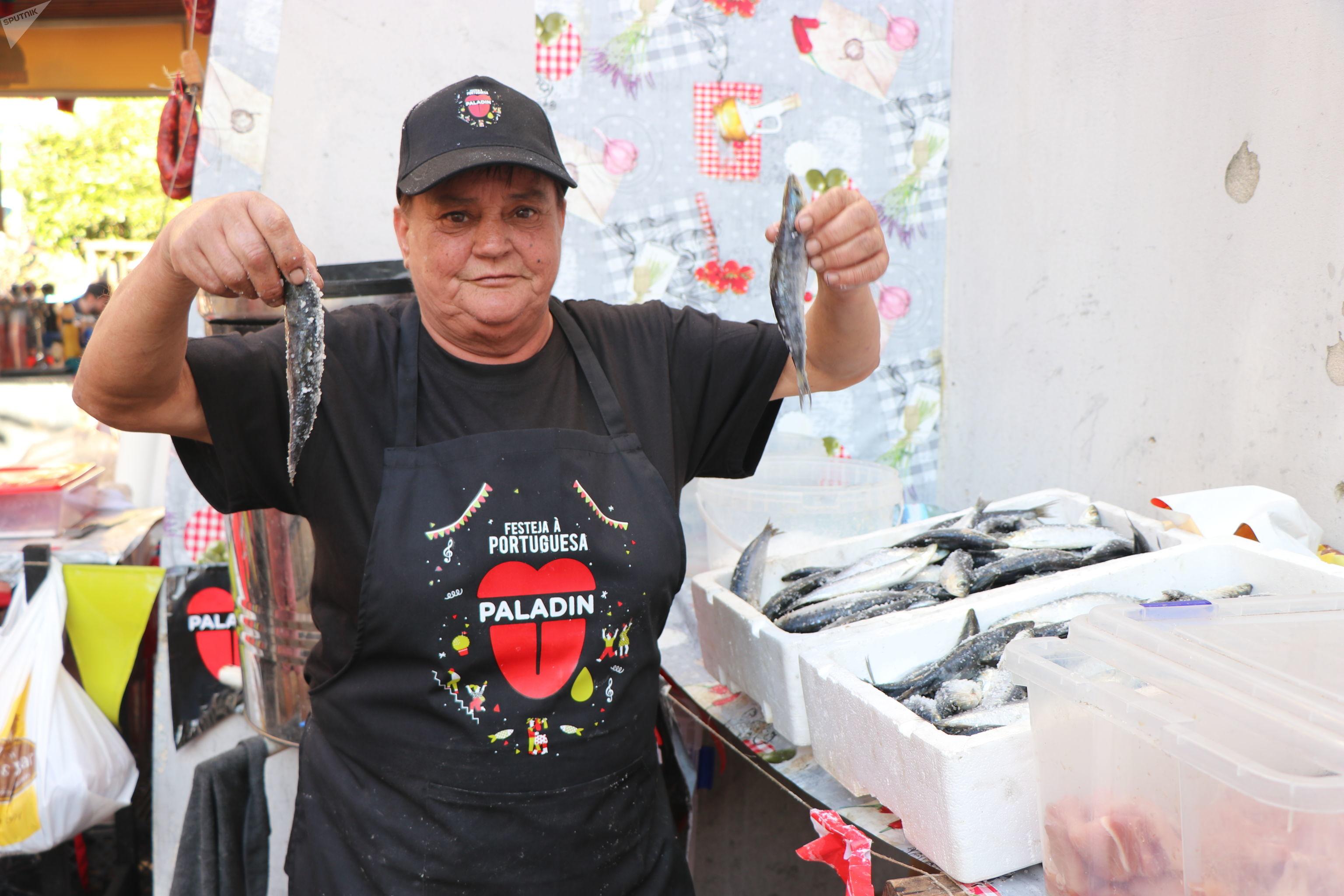 Maria Xuxa do Carmo segurando sardinhas prontas para preparo