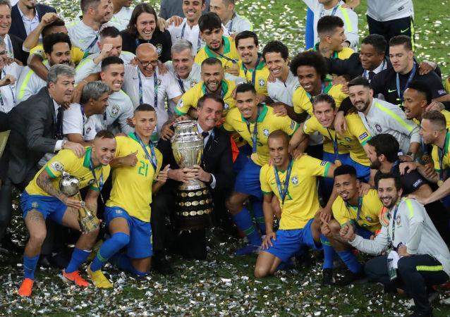Presidente do Brasil, Jair Bolsonaro, se reúne com Seleção Brasileira segurando a taça da Copa América, Rio de Janeiro, 7 de julho de 2019