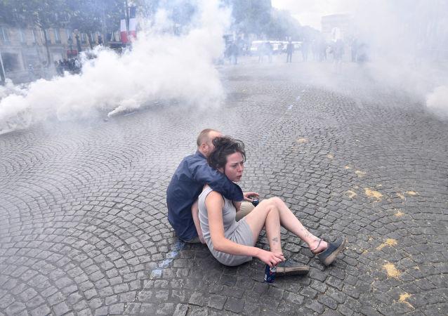Um casal se protege em meio ao gás lacrimogêneo disparado pela polícia em confronto com manifestantes ligados ao movimento dos coletes amarelos após a tradicional parada militar do Dia da Bastilha em Paris