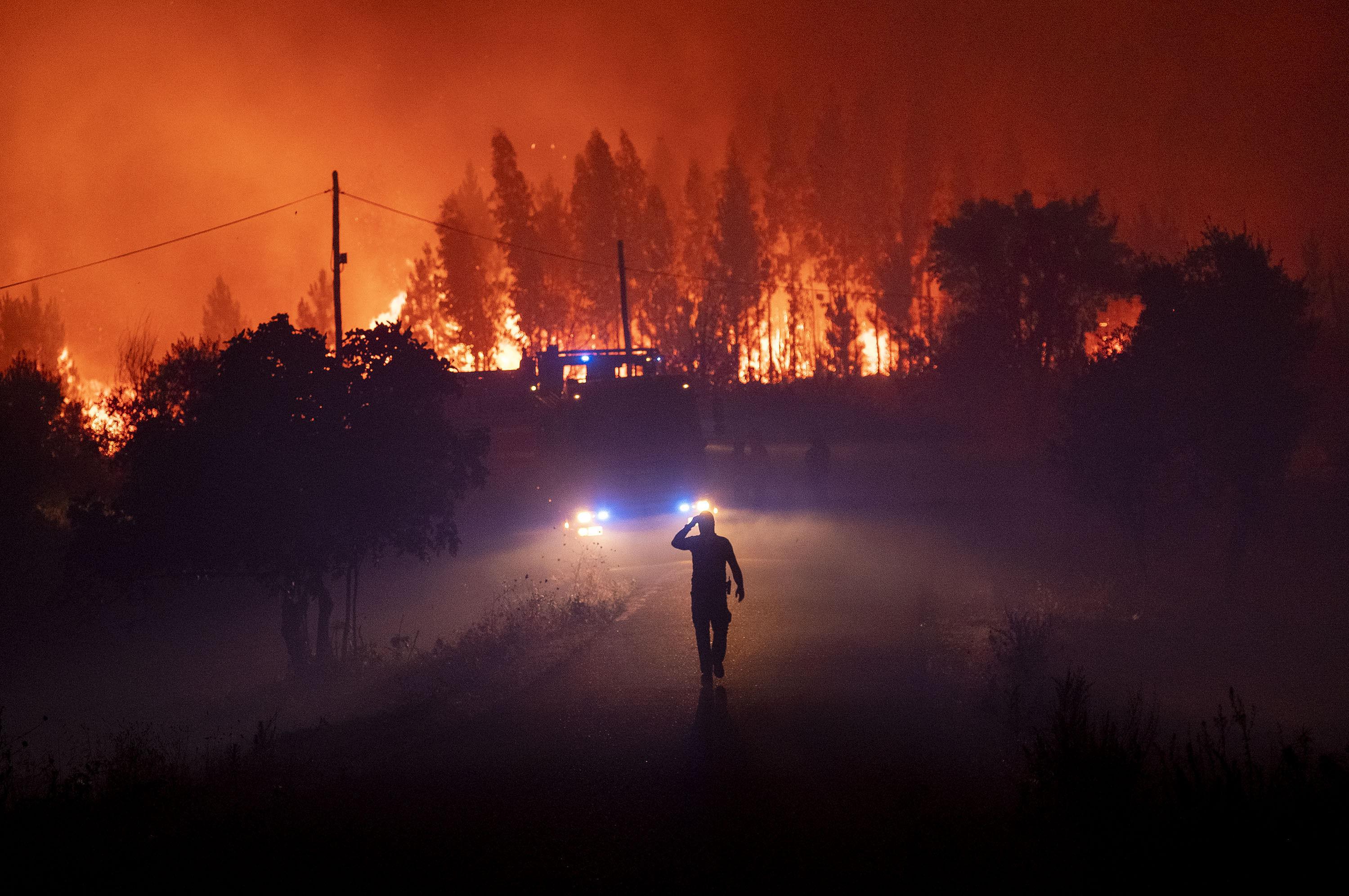 Membros dos serviços de emergência tentam extinguir incêndio perto de Cardigos, Portugal, em 21 de julho de 2019