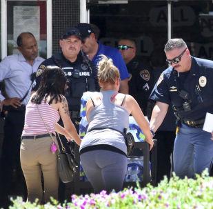 Algumas pessoas entram em uma escola para procurar parentes próximos ao local de um tiroteio em El Paso, no Texas, no dia 3 de agosto de 2019. Dezenas de pessoas foram mortas no incidente.