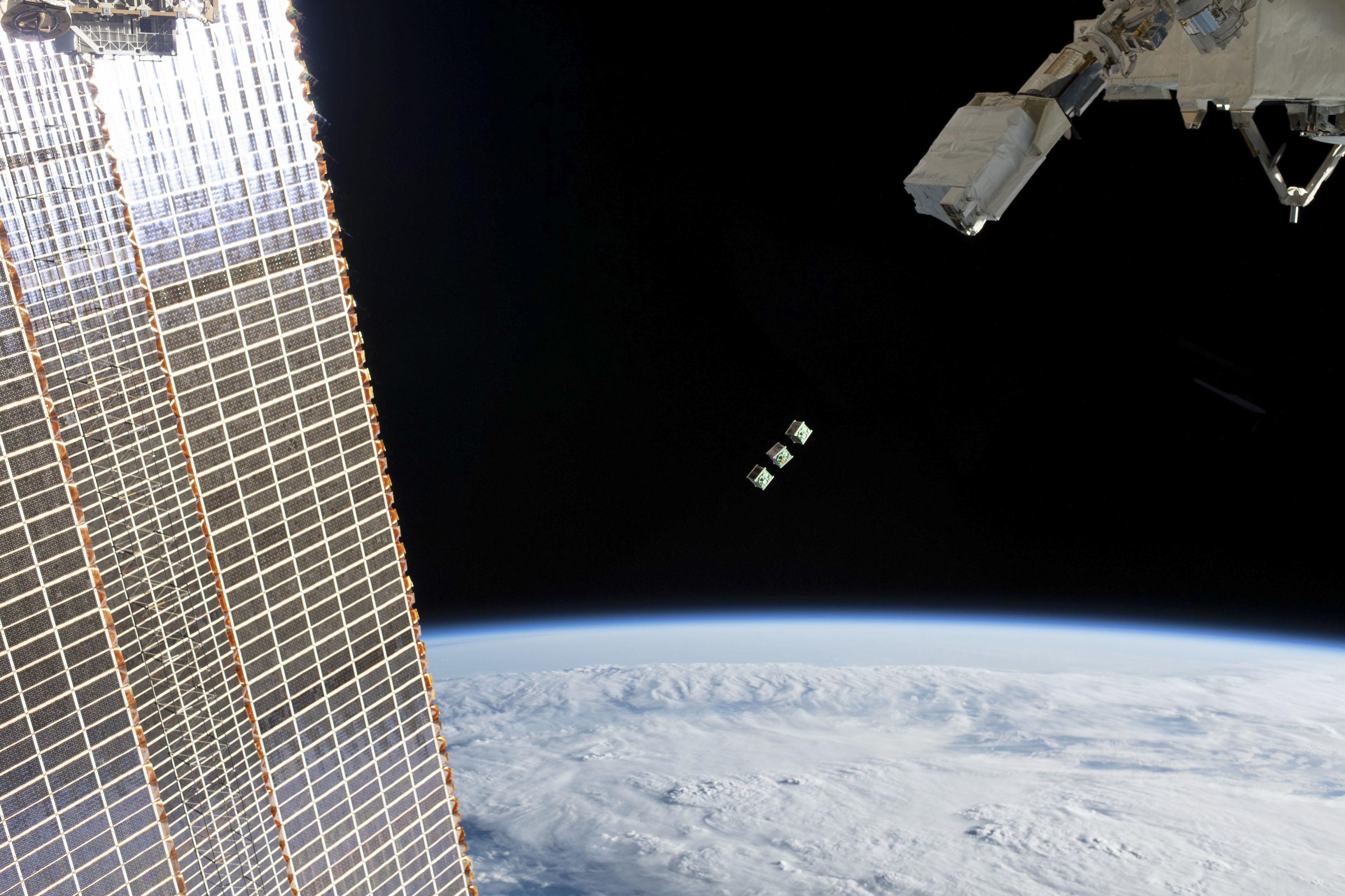 Conjunto de três CubeSats logo após serem ejetados do pequeno satélite orbital Deployer, ligado a um braço robótico no exterior do módulo do laboratório Kibo da Agência de Exploração Aeroespacial Japonesa, 17 de junho de 2019