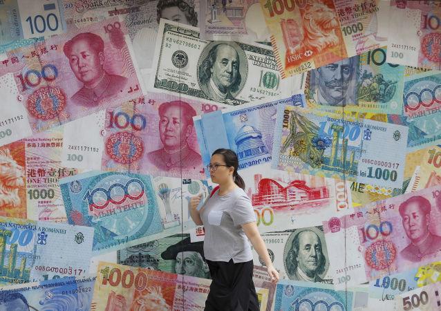 Mulher passa em frente a casa de câmbio em Hong Kong decorada com notas de yuan e dólar