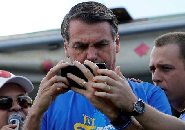 Presidente do Brasil, Jair Bolsonaro, usa celular durante marcha evangélica, Brasília, 10 de agosto de 2019