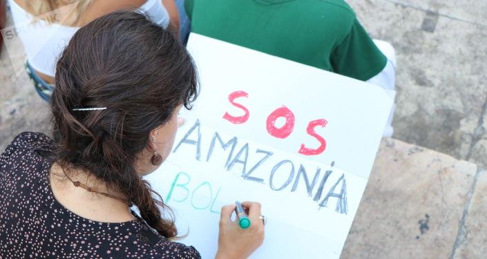 Manifestante escrevendo cartaz durante ato contra queimadas na Amazônia em Lisboa, Portugal