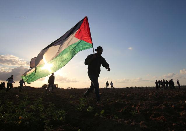 Homem carrega bandeira da Palestina na Faixa de Gaza.