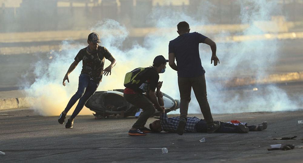 Manifestantes correm para ajudar um homem ferido durante protesto em 5 de outubro de 2019 contra o governo em Bagdá, no Iraque (arquivo)