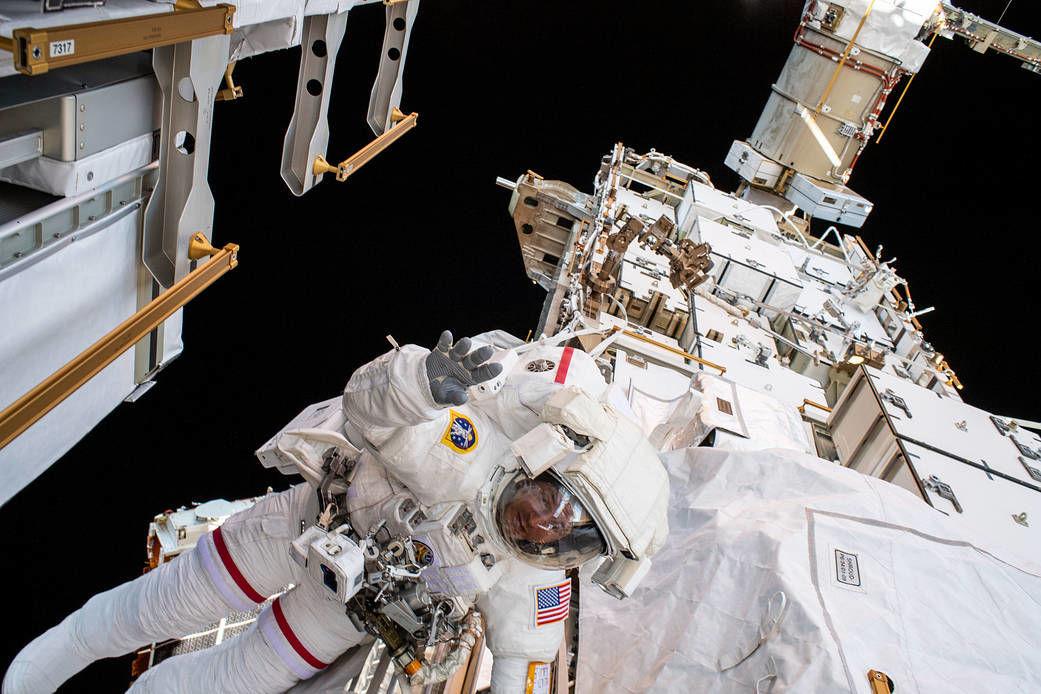 O astronauta da NASA Andrew Morgan acena para a câmera enquanto amarrado na seção P6 da EEI