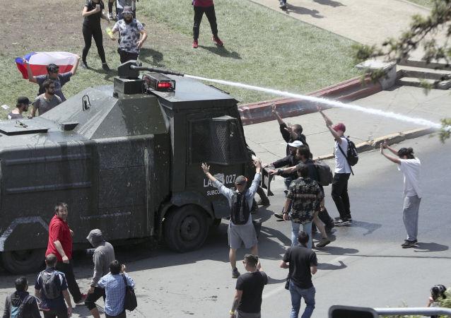 Manifestantes em Santiago, no Chile, confrontam um veículo policial equipado com canhões de água. O registro é do 5º dia de protestos de massa no país, em 22 de outubro de 2019.