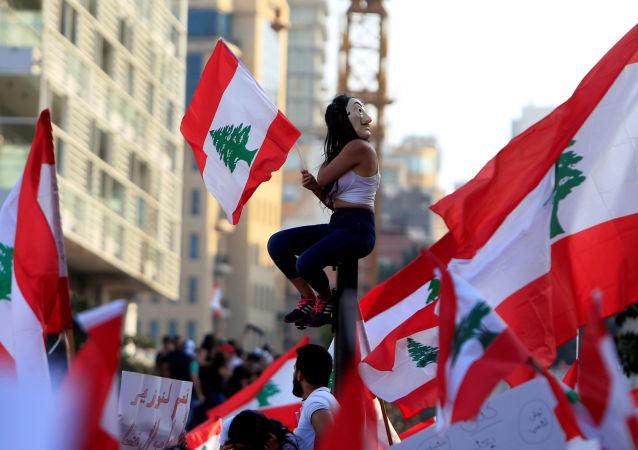 Manifestante sentada sobre um poste carregando uma bandeira do Líbano em Beirute durante protestos no dia 20 de outubro.