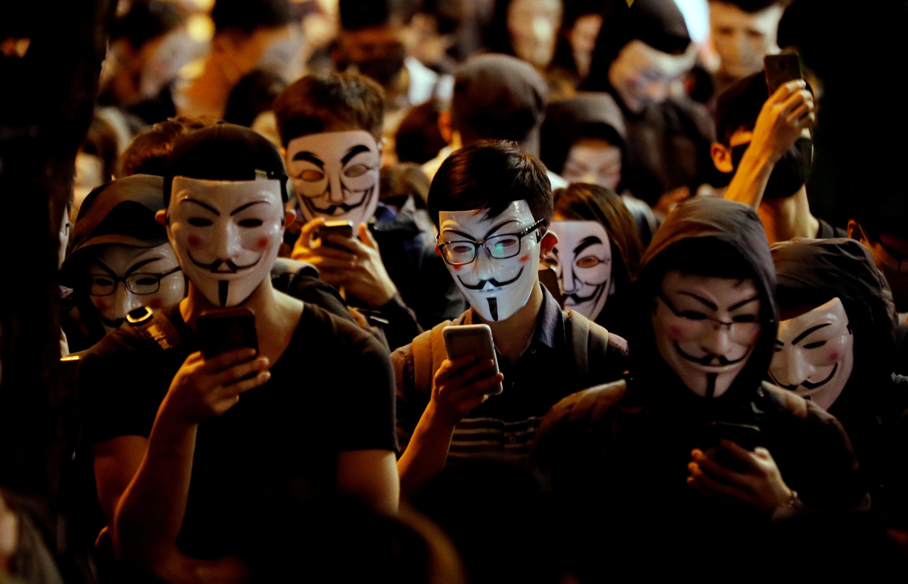 Manifestantes usando máscaras participam de protestos anti-governo em Hong Kong, em 5 de novembro