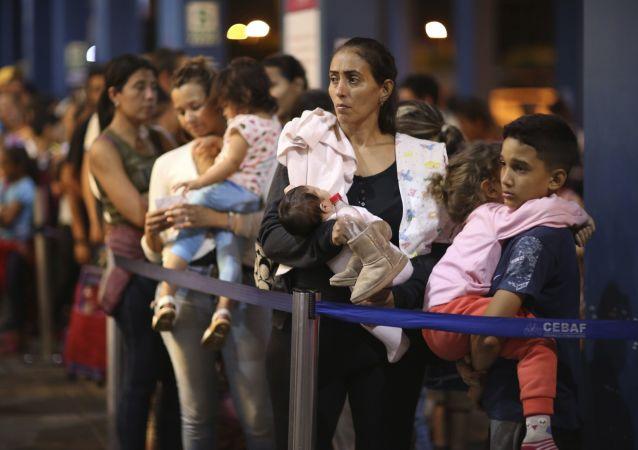 Imigrantes venezuelanos esperando na fila para passar no controle da imigração em Tumbes, Peru, na fronteira com o Equador