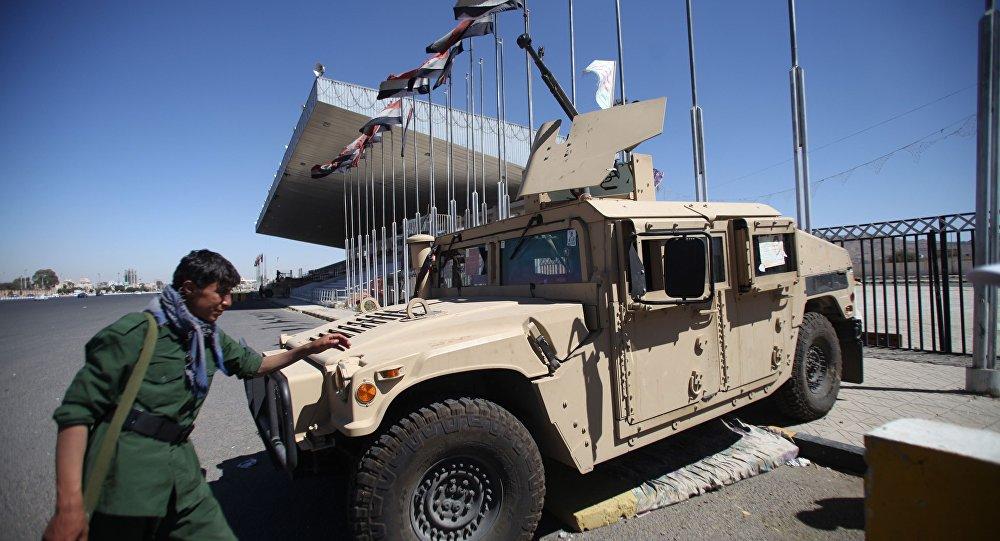Um soldado houthi uniformizado caminha em frente a um veículo militar