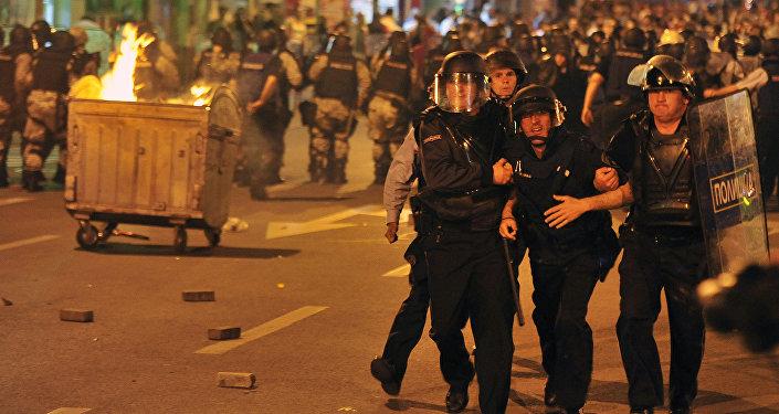 Grupo de policiais transportam seu colega ferido para a ambulância durante protestos de 5 de maio em Skopje; novo protesto é marcado para 17 de maio.