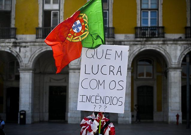 """Homem coberto com fita adesiva segura uma bandeira portuguesa e um cartaz dizendo """"Quem lucra com os incêndios?"""", enquanto centenas de pessoas se juntam na Praça do Comércio, Lisboa, em 21 de outubro de 2017, para protestar contra a resposta do governo aos recentes fogos florestais em Portugal"""