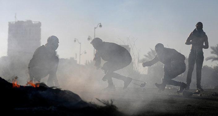 Manifestantes palestinos se escondem durantes confrontos com tropas israelenses perto de povoados judeus