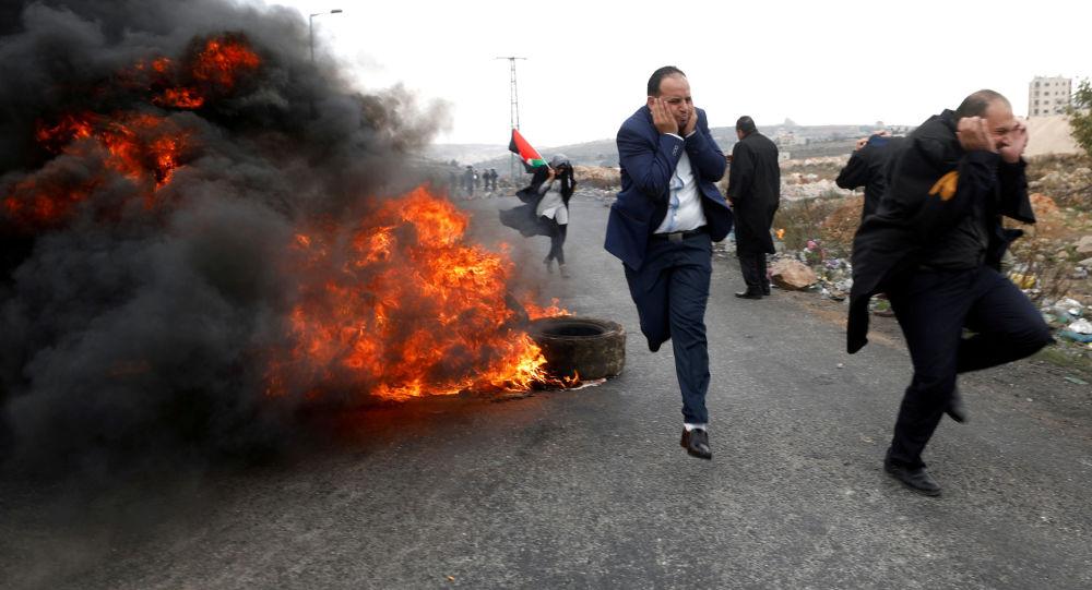 Advogados palestinos fogem durante confrontos com as tropas israelenses durante os protestos contra a decisão de Donald Trump de reconhecer Jerusalém como capital do Estado judeu, em 13 de dezembro de 2017