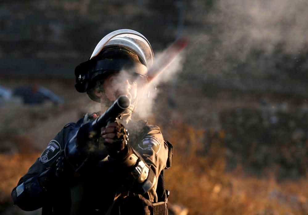 """Um guarda fronteiriço israelense dispara contra manifestantes palestinos durante os confrontos, enquanto estes apelam ao """"dia de ira"""" em resposta à decisão de Donald Trump de reconhecer Jerusalém como capital do Estado judeu, em 13 de dezembro de 2017"""