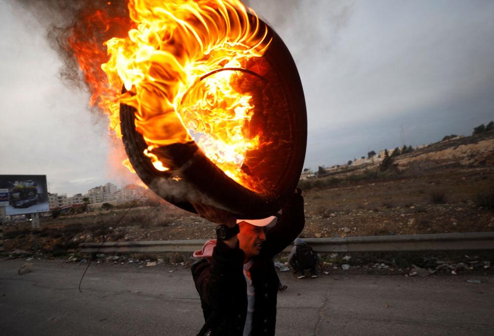 Um palestino segura um pneu em chamas durante os confrontos com as tropas israelenses perto do povoado de Beit El, a pouca distância da cidade de Ramallah, na Cisjordânia, em 10 de dezembro de 2017