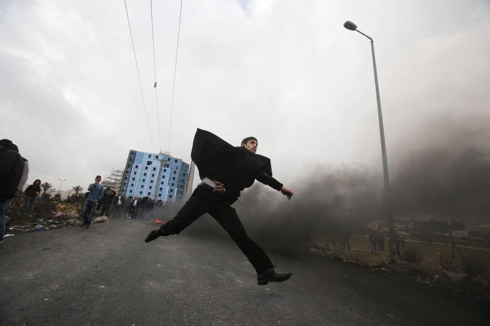 Um advogado palestino atira pedras em direção às tropas israelenses durante os confrontos com as tropas israelenses perto do povoado de Beit El, a pouca distância da cidade de Ramallah, na Cisjordânia, em 13 de dezembro de 2017