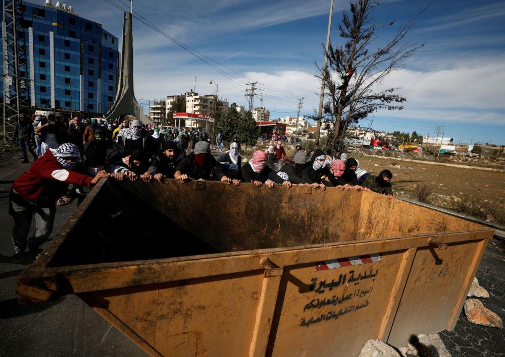 Manifestantes palestinos puxam um contêiner com lixo durante os confrontos com os soldados israelenses perto do povoado de Beit El, a pouca distância da cidade de Ramallah, na Cisjordânia, em 11 de dezembro de 2017