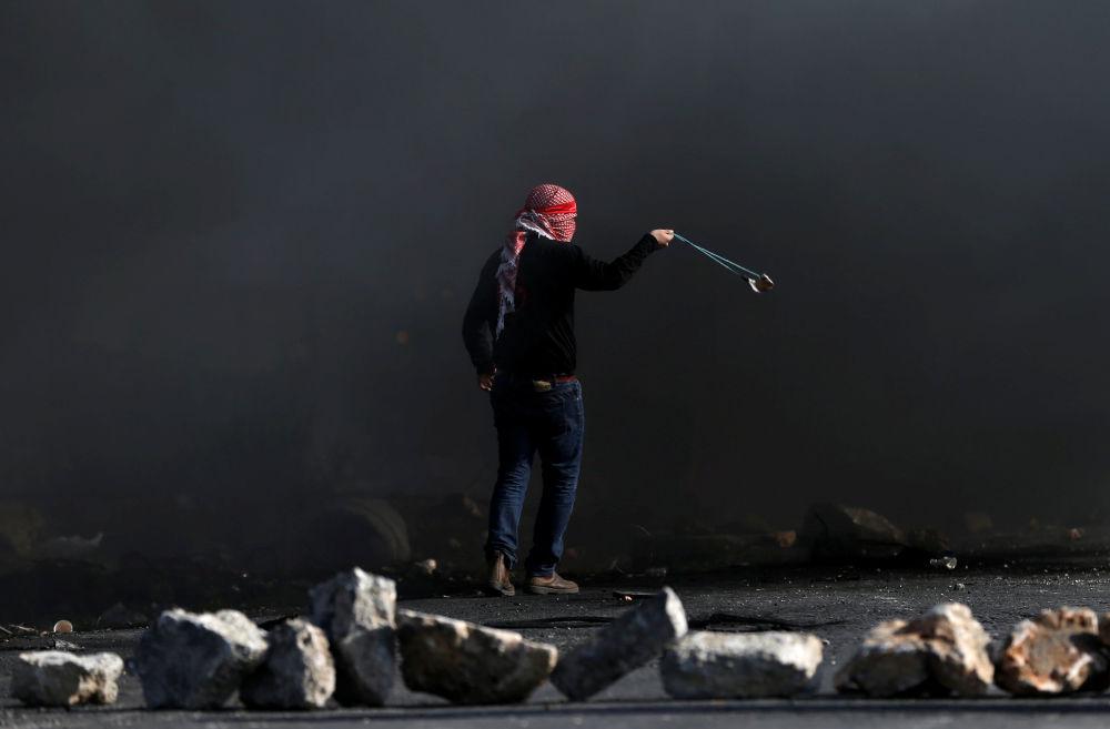 Um manifestante palestino usa bodoque para lançar pedras contra os soldados israelenses durante os confrontos perto do povoado de Beit El, a pouca distância da cidade de Ramallah, na Cisjordânia, em 11 de dezembro de 2017