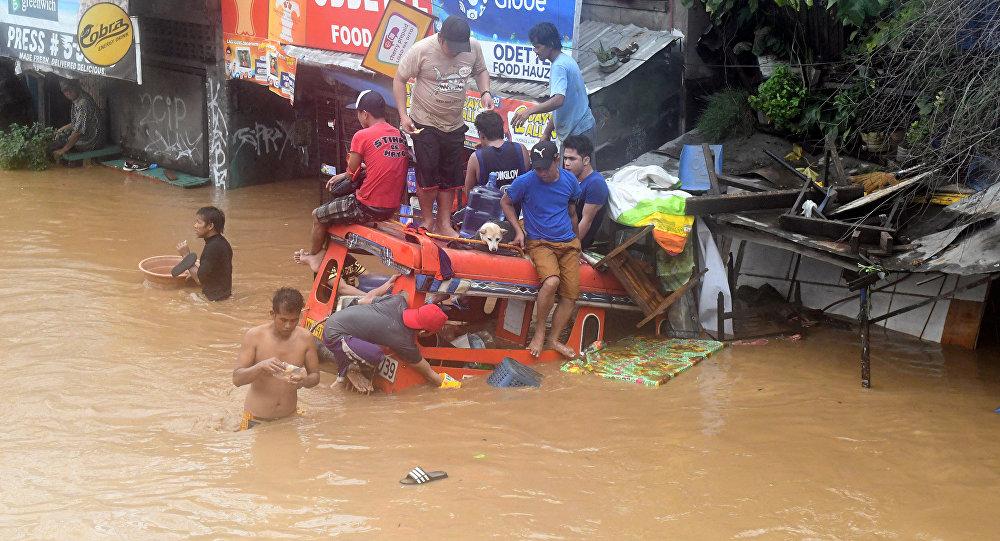 Filipinos estão sentados em um veículo parcialmente afundado em uma das ruas inundadas na sequência da tormenta, em 22 de dezembro de 2017