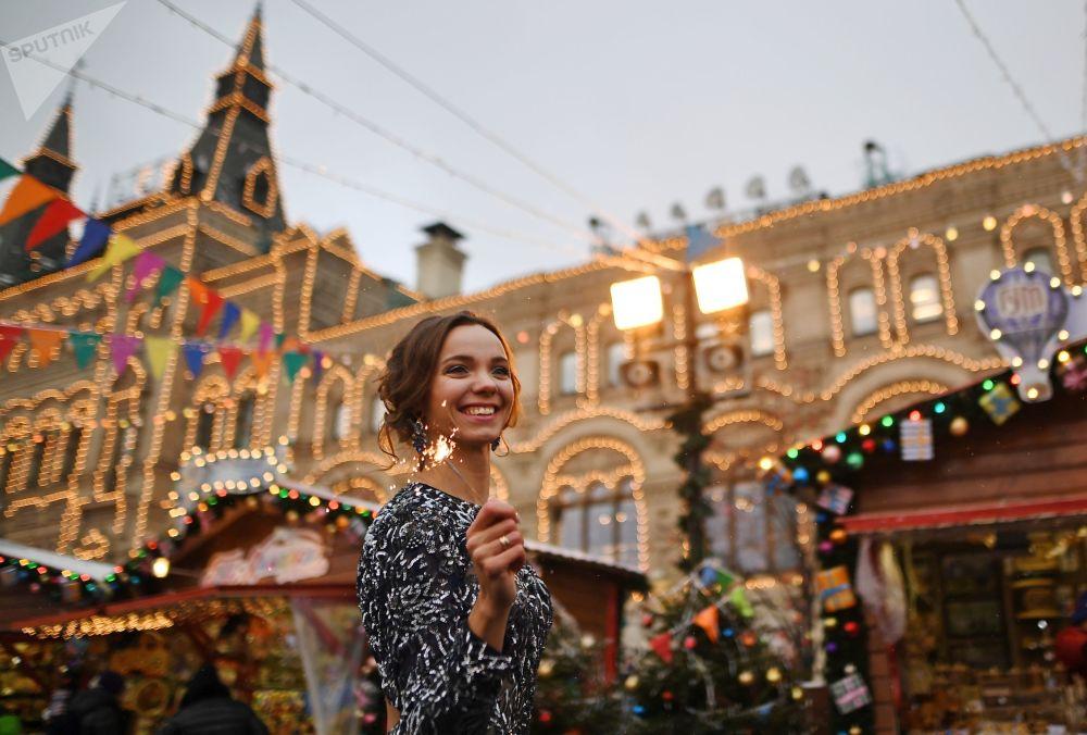 Menina em uma feira natalina perto do edifício emblemático do centro comercial GUM, na Praça Vermelha