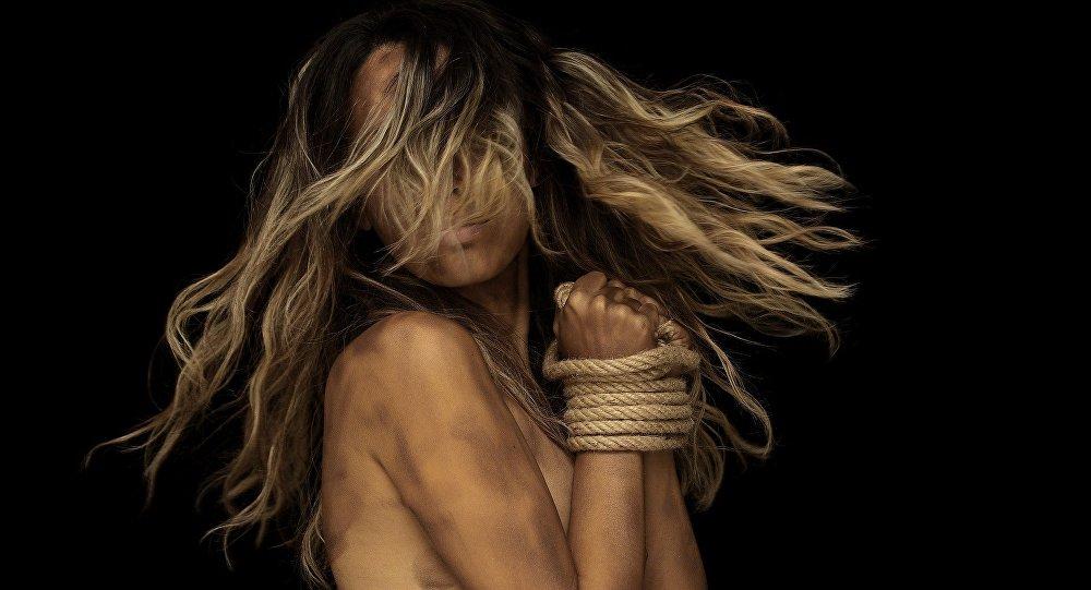 Uma mulher com as mãos amarradas