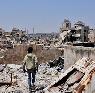 Menino sírio em meios às ruinas no norte de Aleppo (foto de arquivo)