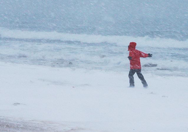 Homem passeia ao longo da costa durante tempestade de neve, imagem referencial
