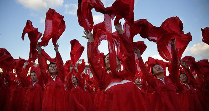 Mulheres dançando durante um desfile militar em Pyongyang por ocasião do 70º aniversário do partido do poder norte-coreano, 10 de outubro de 2015
