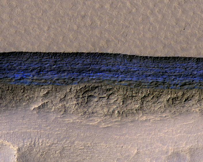 Uma seção transversal de gelo subterrâneo em uma escarpa, marcada em azul brilhante, imagem captada pela câmara HiRISE da Mars Reconnaissance Orbiter
