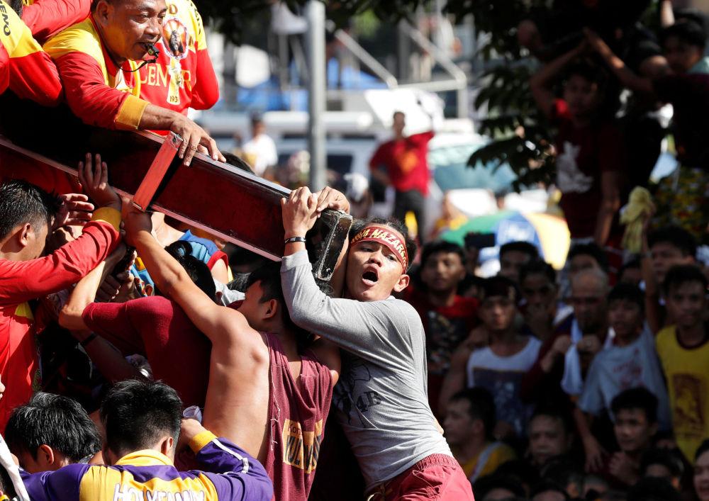 Menino segura cruz com Cristo Negro durante processão anual religiosa em Manila, Filipinas