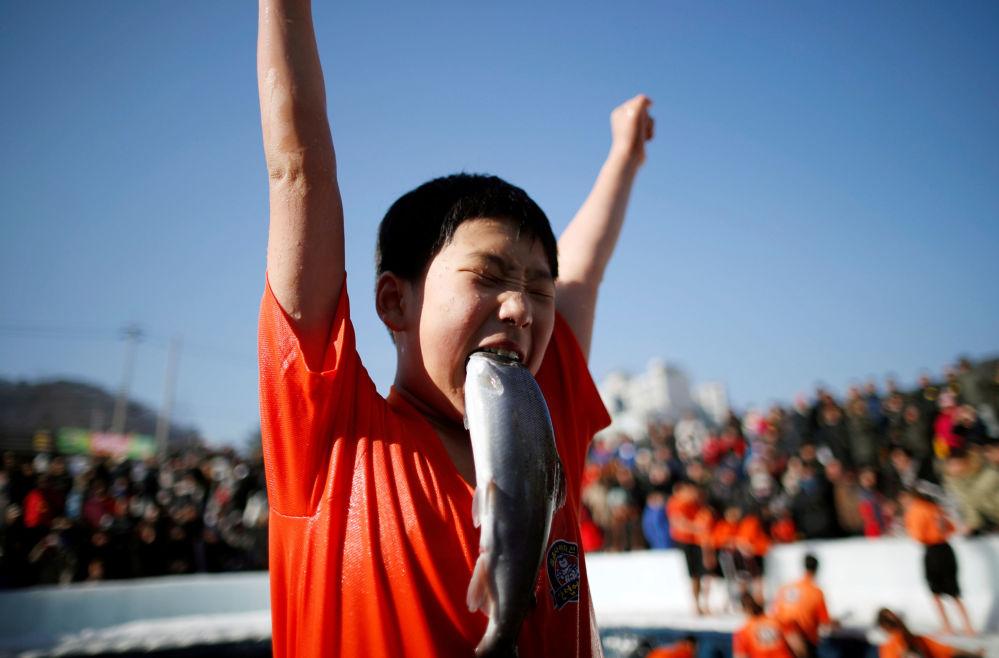 Menino contente por ter apanhado um peixe com as mãos na cidade sul-coreana de Hwacheon