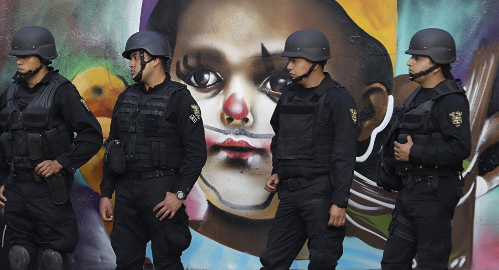 In this Monday, Jan. 9, 2017 photo, police providing security walk past street art as thousands march against the government of Enrique Pena Nieto following a 20 percent rise in gas prices in Mexico City.