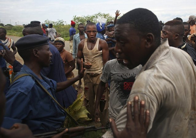 Manifestantes protestam de policial acusada de atirar em uma pessoa no bairro de Buterere, em Bujumbura, Burundi