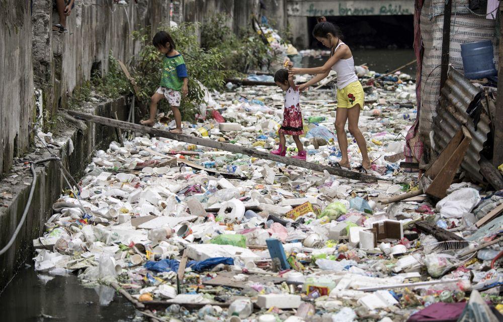 Residentes atravessam montes de lixo por uma tábua de madeira em Manila, nas Filipinas