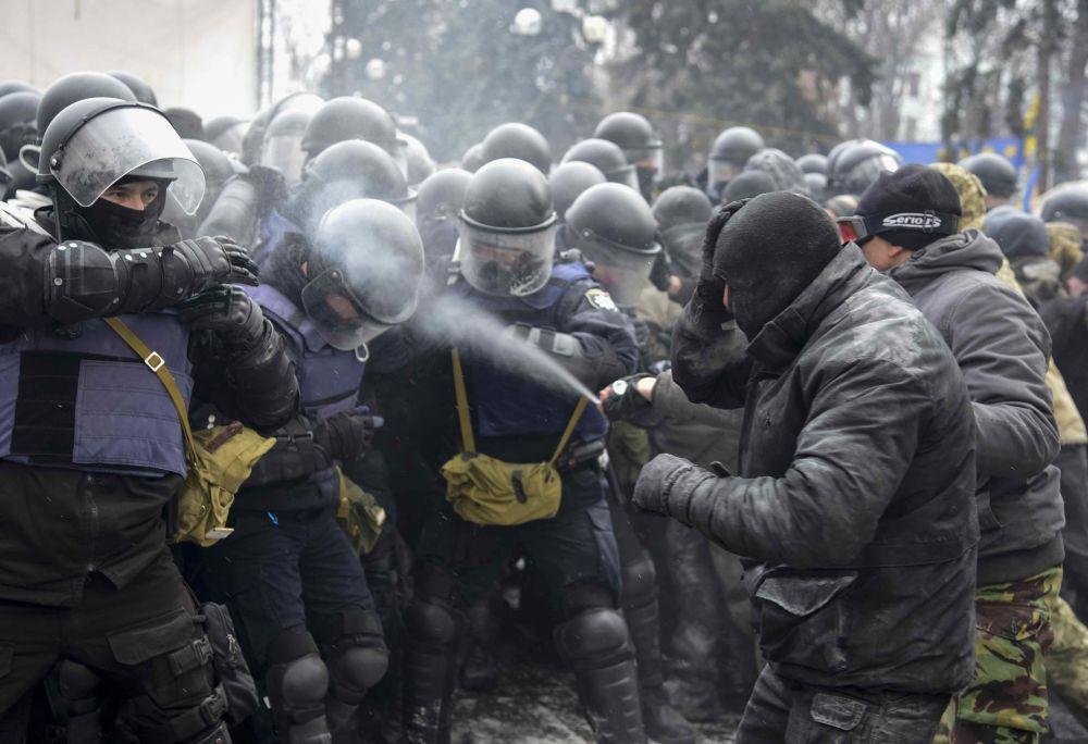 Homem lança gás lacrimogêneo contra um policial no campo dos apoiantes de Mikheil Saakashvilli perto do parlamento em Kiev