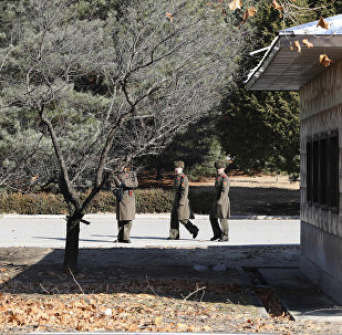 Three North Korean soldiers look at the South side at the spot where a North Korean soldier crossed the border at the Panmunjom in the Demilitarized Zone, South Korea