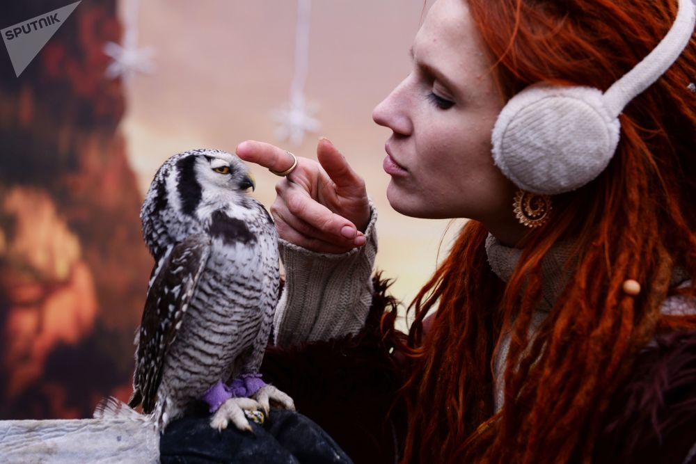 Funcionária do centro de fauna da cidade russa de Sochi acaricia coruja