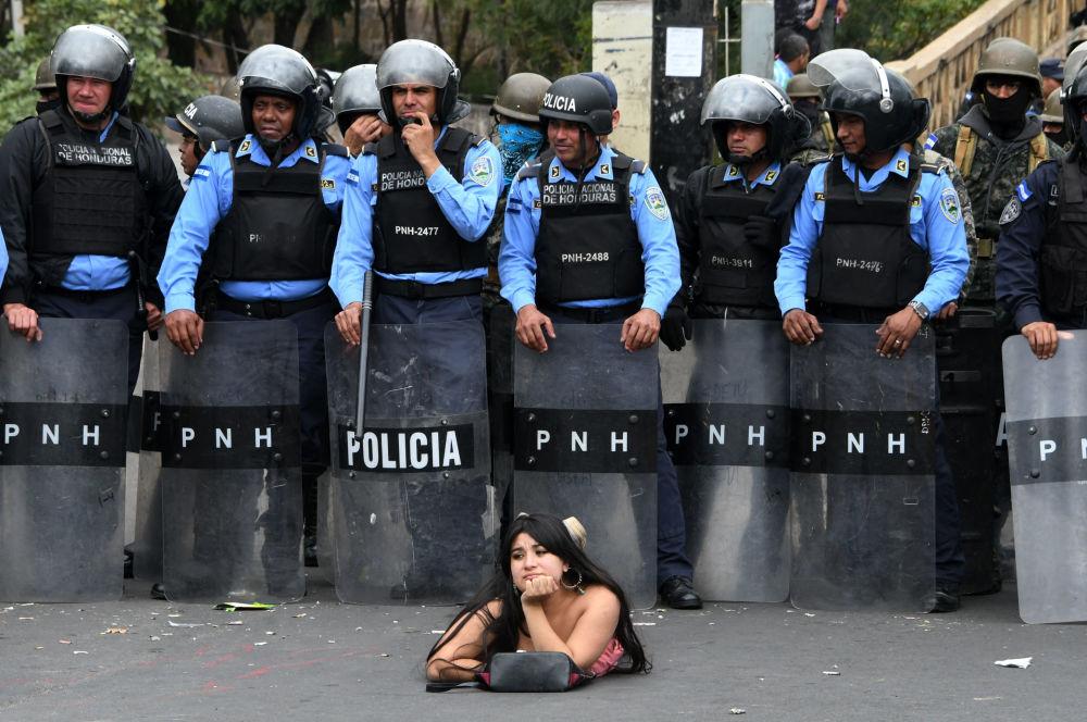Apoiante do candidato de oposição à presidência hondurenha, Salvador Nasralla, entre policiais durante uma manifestação contra a reeleição do presidente Juan Orlando Hernandez