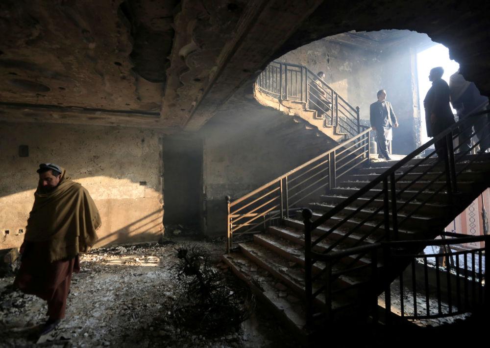 Homem afegão inspeciona edifício destruído na sequência de uma explosão em Jalalabad, no Afeganistão