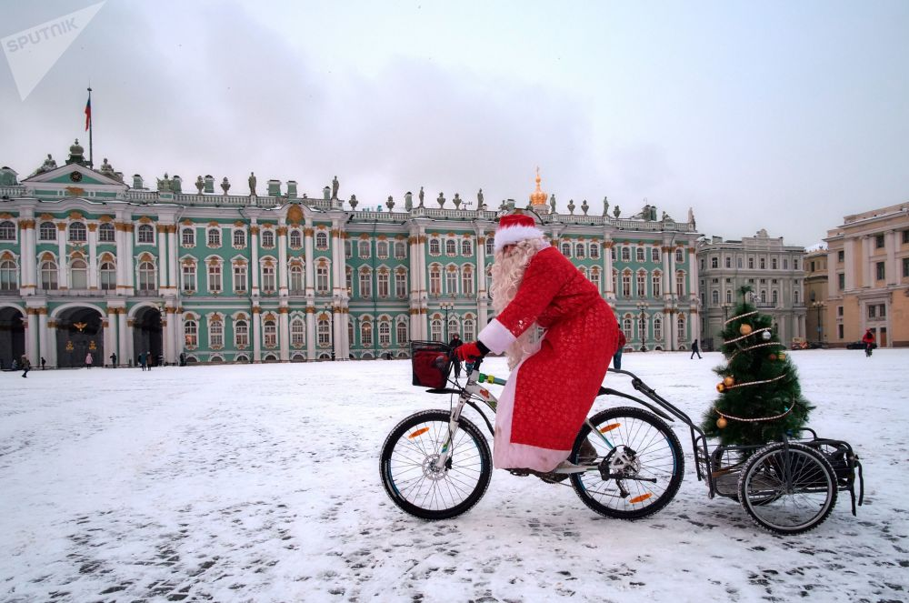 Competidor termina a corrida de bicicleta de Papais Noéis na Praça do Palácio em São Petersburgo