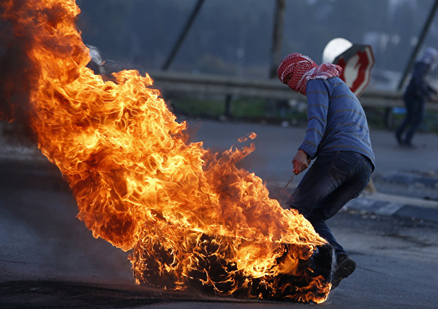 Manifestante palestino com um pneu em chamas durante confrontos com as forças de segurança israelenses na cidade de Nablus, na Cisjordânia
