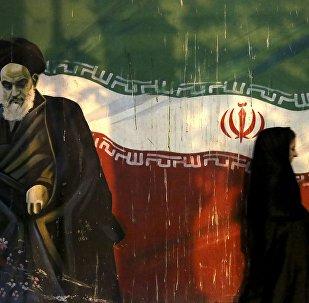 Iraniana coberta passa por muro que retrata o revolucionário aiatolá Khomeini e a bandeira iraniana nacional, pintada na parede da antiga embaixada dos EUA, em Teerã, Irã