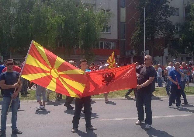 Manifestantes mostram bandeiras da Macedônia e do Kosovo no domingo (17 de maio) em Skopje.