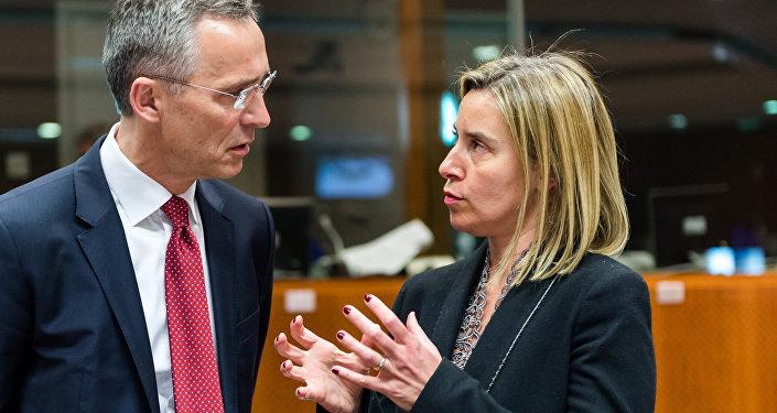 Secretário-geral da OTAN, Jens Stoltenberg (esquerda) e chefe da diplomacia europeia, Federica Mogherini (direita), discutem começo da operação militar no Mediterrâneo