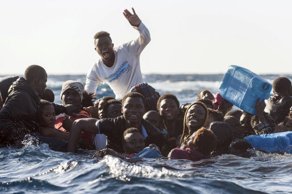 Migrantes em um barco semiafundado pedem socorro no mar Mediterrâneo